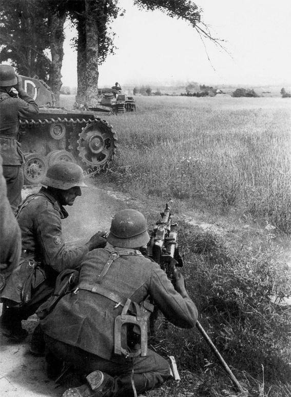 The machine gun crew of the German rangers is firing from the MG-34 machine gun. Summer 1941 of the Year, Army Group North. In the background, the calculation covers the ACS StuG III. Shooting time: summer 1941