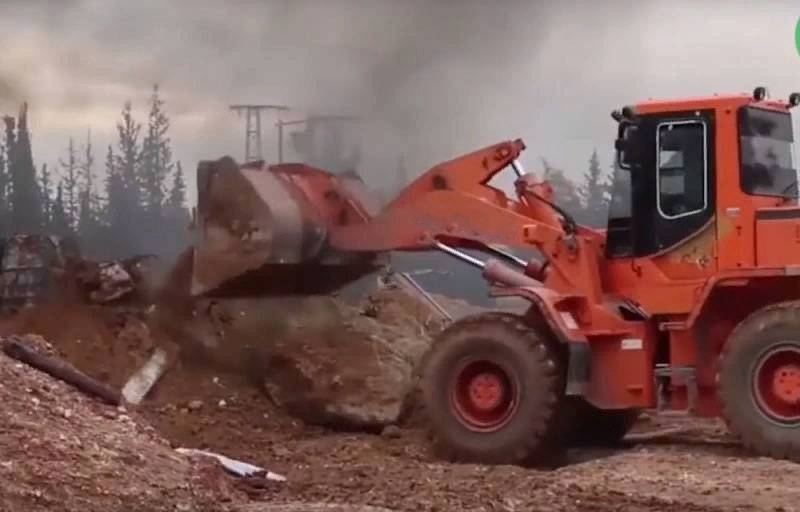 Syria, March 20: Turkish bulldozers and militants clear M4 highway in Idlib