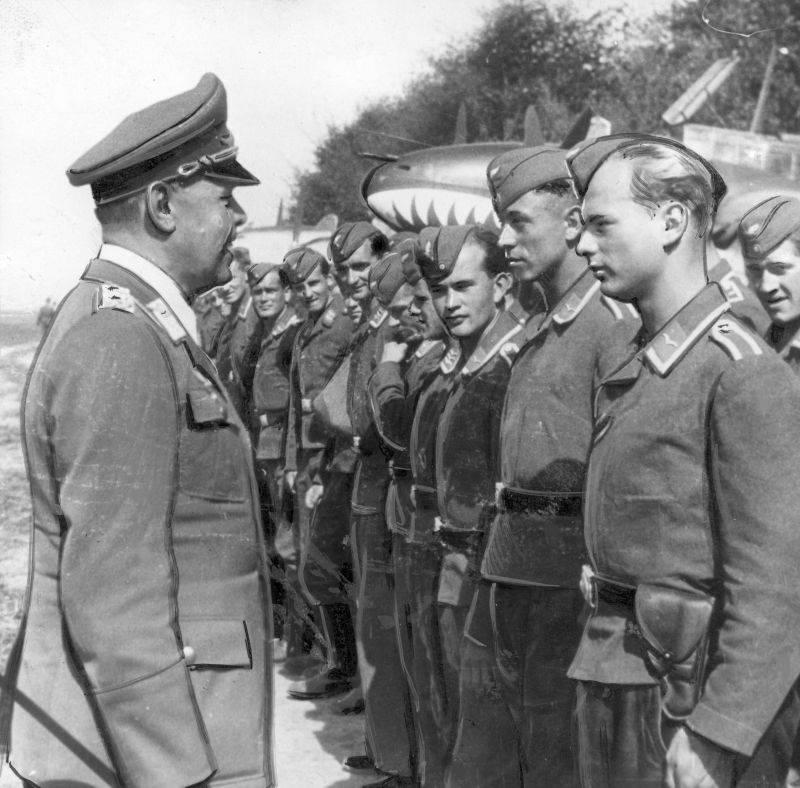 Командующий 2-м воздушным флотом люфтваффе генерал-фельдмаршал Альберт Кессельринг во время встречи с летчиками 76-й эскадры тяжелых истребителей. На заднем плане стоит истребитель Bf.110C-1 «Мессершмитт»
